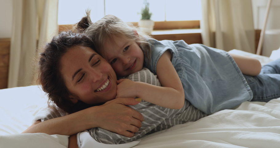 Affectionate family cute adorable funny little kid daughter embrace kiss young mom lying relaxing on bed, happy loving mother and small child girl enjoy bonding hugging having fun playing in bedroom