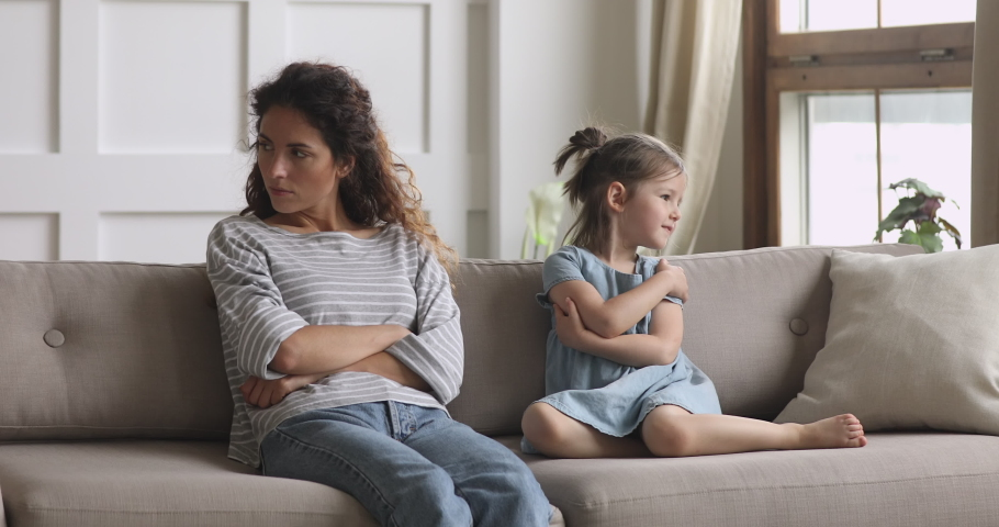 Unhappy stubborn young adult mother and little small child daughter turn back sit on couch ignore each other feel angry not talking after family conflict fight, parents and children argument concept | Shutterstock HD Video #1039338251