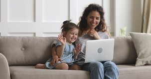 Happy parent mother and cute small child daughter looking at laptop screen webcam having fun using funny face mask effects making conference video call chat at home relaxing laughing sitting on sofa