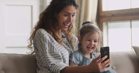 Cute funny little kid girl having fun with mom enjoy using modern gadget smart phone looking at mobile screen laughing making conference call in app, watching social media video sit on couch at home