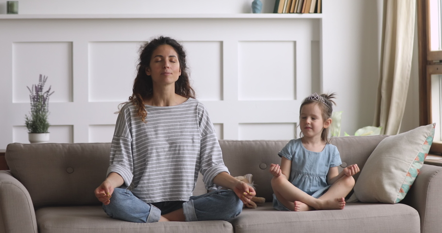 Funny cute little kid daughter meditating in lotus pose laughing with young mom at home, happy healthy family mother and small child girl having fun doing yoga exercise relaxing together sit on couch