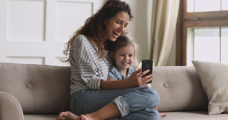Happy family mum and cute little kid daughter laugh use smart phone funny face mask app look at cell screen, mother with child take selfie watch cartoons make video call on mobile sit on sofa at home
