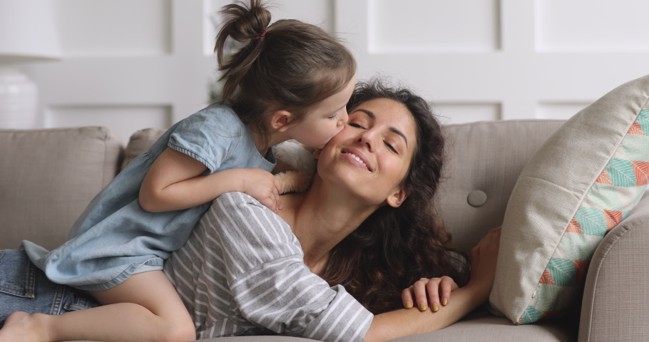 Cute adorable funny little kid daughter tickling caressing young mum kissing on cheek playing on sofa at home, happy family mother and small child girl wear crown enjoying bonding having fun on couch