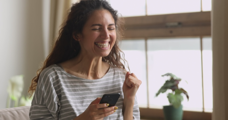 Excited young woman hold phone chatting in dating app feel happy sit on sofa, euphoric overjoyed lady winner celebrate mobile online bid game win victory success receive read good news on cellphone
