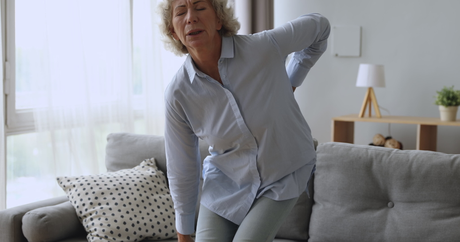 Upset worried senior adult woman feel sore back ache getting up from sofa, tired elderly grandma touching spine suffer from osteoarthritis lower lumbago spinal backache, older people backpain concept