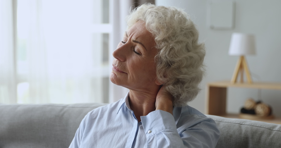 Unhappy tired senior old woman rubbing neck feeling pain sit on couch at home, upset elderly grandma massaging stiff muscles suffering from osteoarthritis osteochondrosis fibromyalgia ache concept