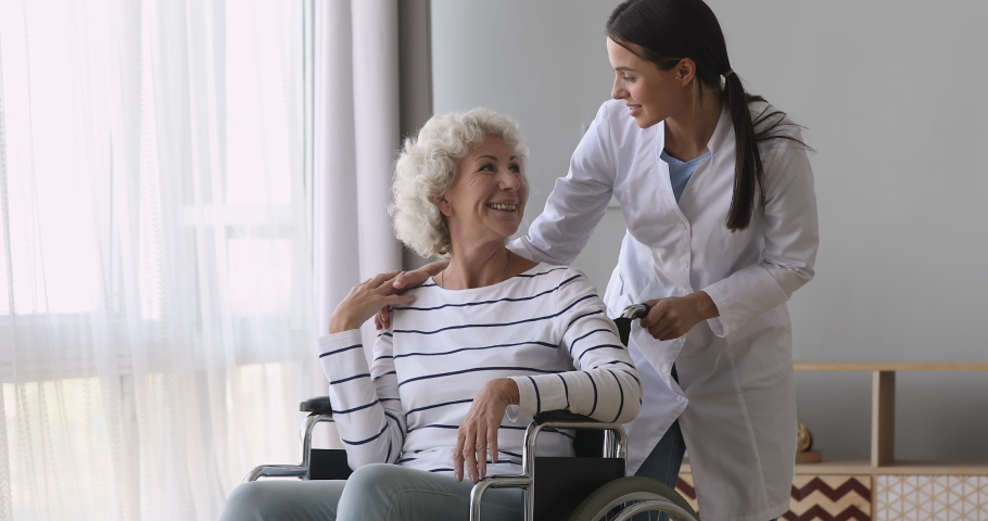 Young woman nurse caregiver talk help disabled handicapped old grandma patient sit on wheelchair at home, female doctor provide elderly lady medical service, senior people health care support concept Royalty-Free Stock Footage #1039338371