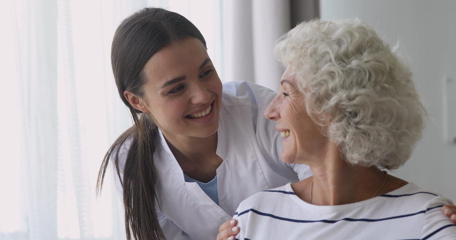 Happy young woman nurse caretaker helping talking with senior grandmother patient give support empathy, female doctor carer having trust conversation with elderly lady, older people homecare concept