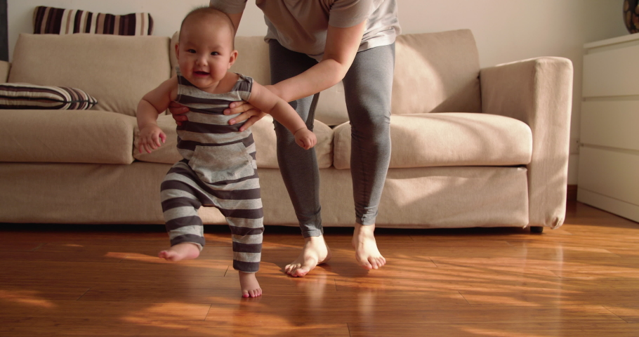 Baby first step Slow motion of 6 months baby learning to walk at home mother holding baby arm walking on the floor indoor with sunlight coming family with baby lifestyles