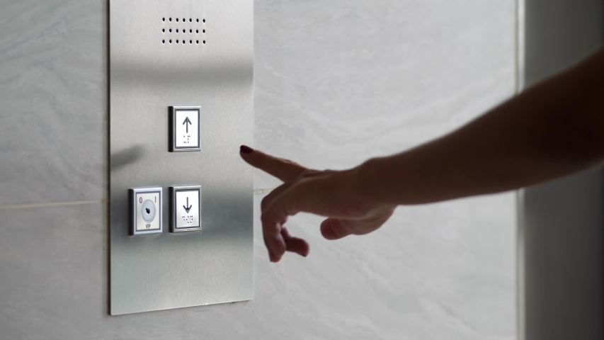 Female Hand Pushing Elevator Button in Office Center or Hotel. Young Woman Pressing Lift Button Down. 4K.