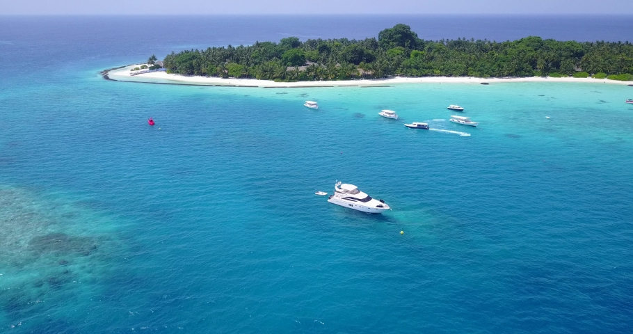 Aerial view video taken by drone of boat cruising in The Maldives lagoon beach with blue turquoise waters #1039373465