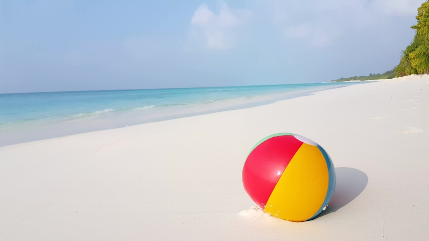 Family summer vacation concept. Colorful beach ball on the white sand beach and turquoise sea water on a tropical island