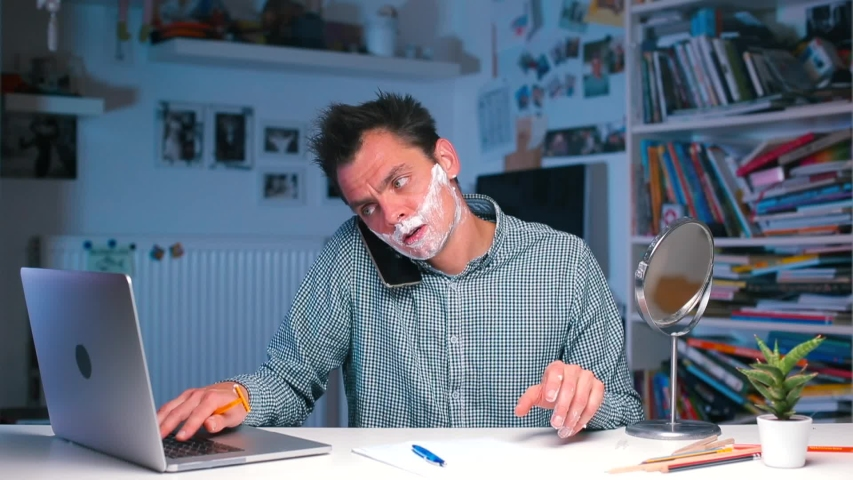 Businessman at the table doing a lot of things. Shaves, speaks on the phone, takes notes. The concept of multitasking at the workplace in the office. Home office in self isolation COVID 19.   | Shutterstock HD Video #1039394228