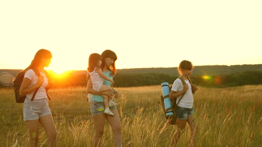 Mom travels with her daughters. mother and children are tourists. girls travel across field in sunset light. family walks in meadow. girls travel with backpacks on country road. | Shutterstock HD Video #1039400585