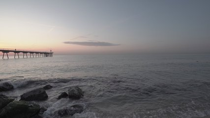 4K clip of bird flying over the mediterranean sea at sunrise in Barcelona, Spain with a concrete bridge in the background and waves crashing on the rocks in the foreground with beautiful light.