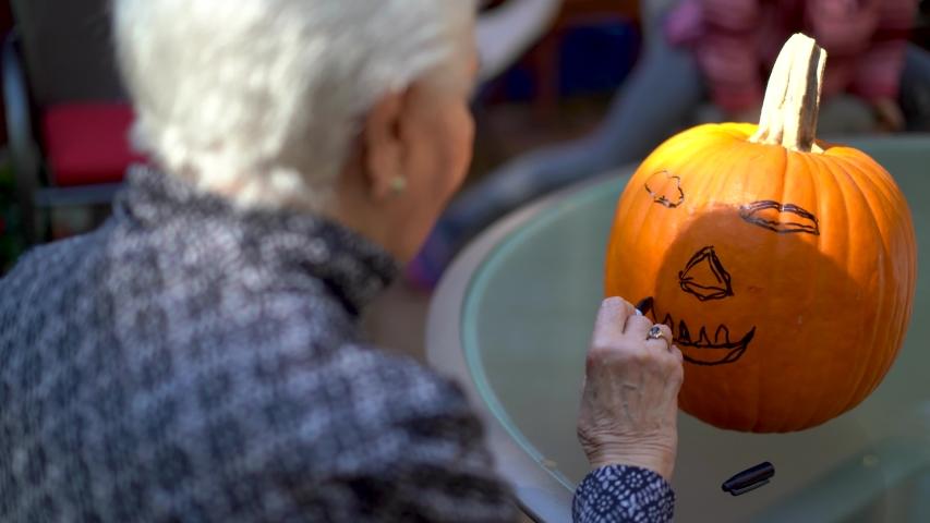 Closeup of pumpkin face elderly woman is drawing on a pumpkin with a marker. | Shutterstock HD Video #1039421834
