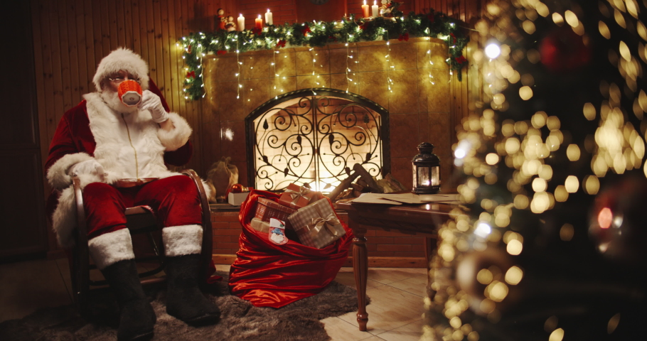 Authentic santa claus sitting in his rocker near christmas tree and srinking tea or cocoa - christmas spirit, holidays and celebrations concept 4k footage | Shutterstock HD Video #1039427501