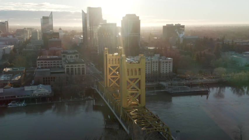 Aerial drone right parallax of Tower Bridge and Downtown Sacramento, CA, including Old Sacramento & State Capitol in background during sunrise.