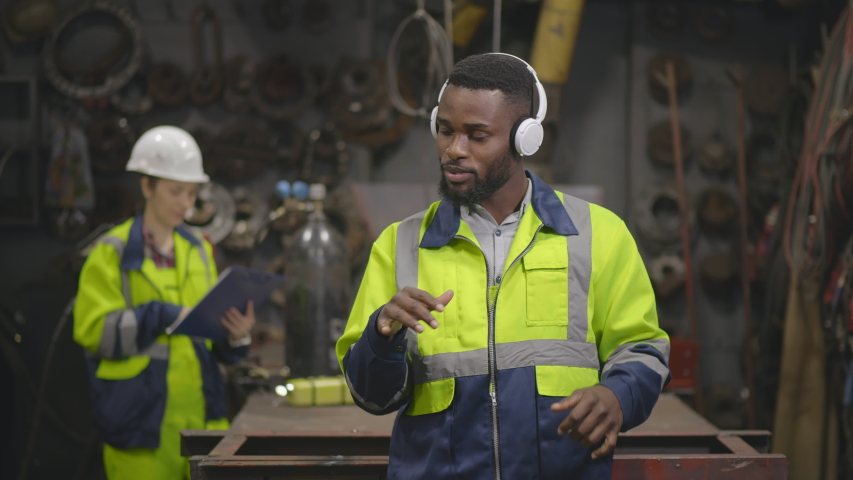 Handsome African American factory worker wearing hardhat and overall listening to music in headphones and dancing while standing in workshop   Shutterstock HD Video #1039430537
