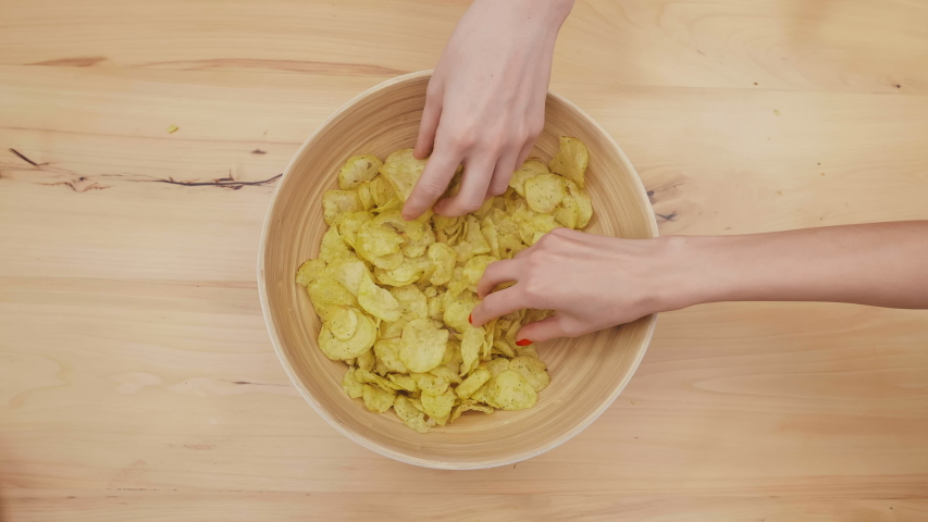 View of potato chips bowl from above. Close up hands of different people that take chips from bowl and it becomes empty   Shutterstock HD Video #1039446809