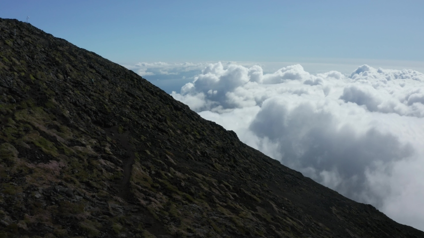 Drone aerial view of the steep slope of Pico Mountain above the clouds. Highest peak of Portugal in Azores