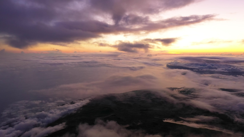 Panning of amazing view, above clouds, from Pico Mountain top on Azores island at sunset.