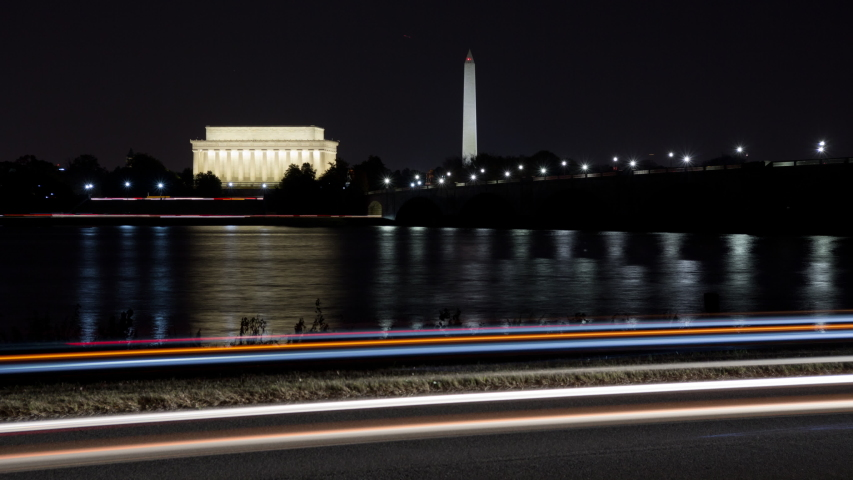 4K time lapse of traffic light streaks around the Lincoln Memorial, Washington Monument and the memorial bridge in Washington D.C. reflecting in the Potomac river and viewed from Virginia at night