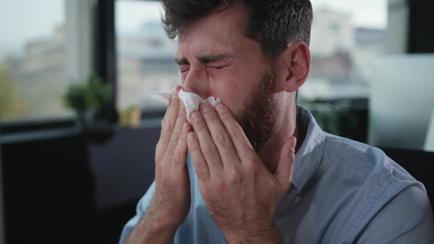 Sick office manager suffering bad allergic feeling sneezing using paper tissues trying to work. Overworked employee portrait. Royalty-Free Stock Footage #1039460756