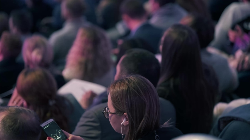 Business conference attendees sit and listen to lecturer, rear view #1039466795