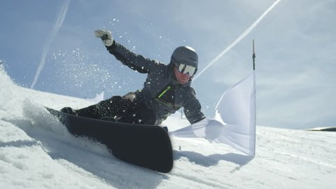 SLOW MOTION CLOSE UP: Racing snowboarder riding slalom between gates