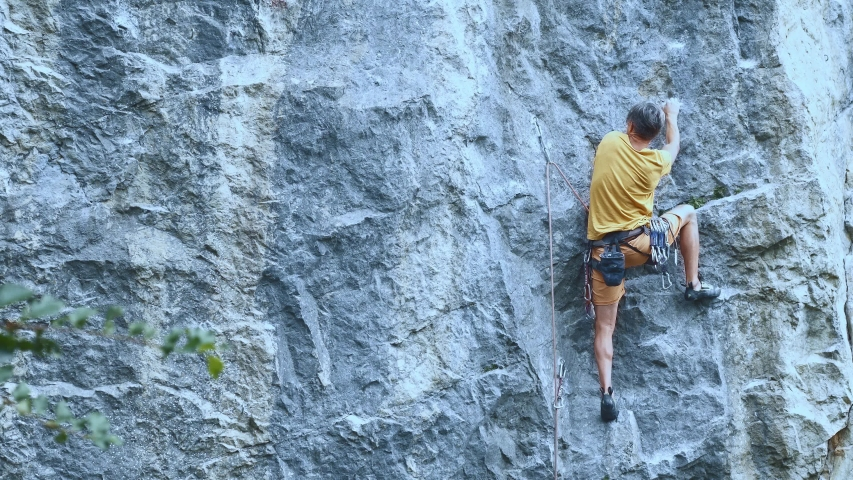 Man rock climber carefully climbing on a cliff, searching, reaching and gripping hold. outdoors rock climbing and active lifestyle concept, 4K stock footage | Shutterstock HD Video #1039477205