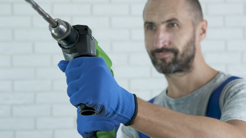 Work with screw driver. A worker with a drill makes a hole. #1039484942