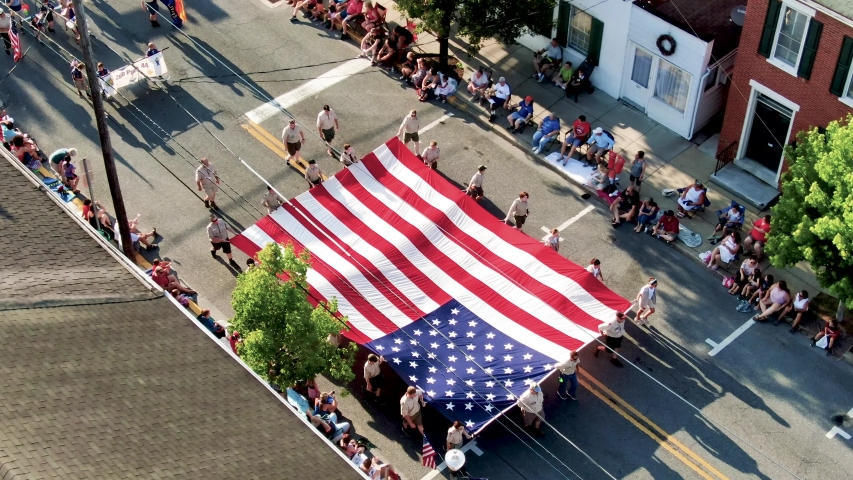 Lititz , PA / United States - 07 04 2019: Tilt down pan aerial shot of Boy Scouts of America carrying start spangled banner American flag in small town parade