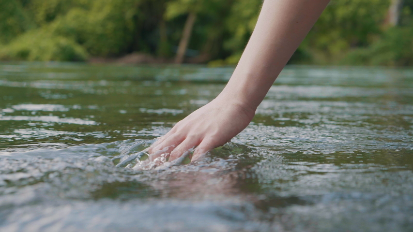 Close up woman hand gently touches the surface of the water in the forest river or lake
