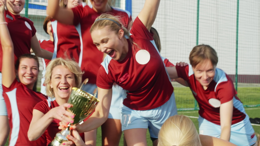 Happy women in soccer sportswear getting Cup, celebrating win and hugging each other Royalty-Free Stock Footage #1039501643