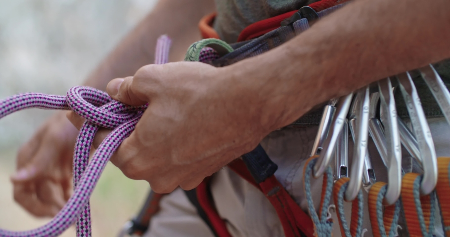 Climber man preparing for climbing up the rocky wall rift by checking rope. Climbing extreme active sport activity. Active people, outdoor activities.Rope detail shot.Slow motion 4k video.
