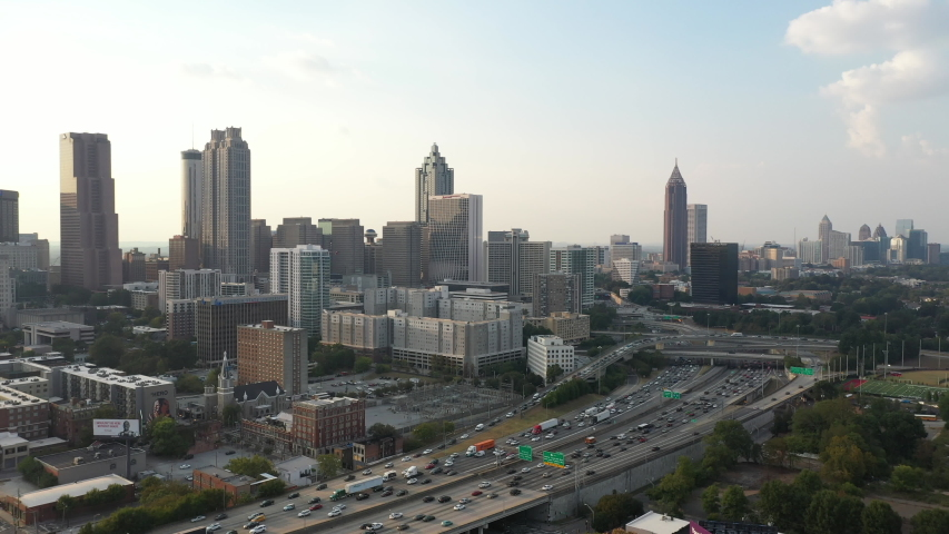 4K Ariel Drone Shot Over Skyline Buildings In Atlanta, Georgia. USA. Pretty Tall Skyline Over Busy Highway Road With Cars Driving Through. Important Tall Buildings, Blue Sky In America