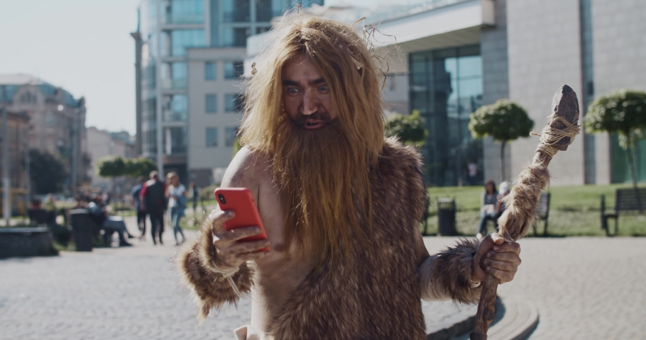 Smiling neanderthal of hunter-gatherers discovering modern device use mobile phone in modern city civilization cro-magnon device evolution future homo sapiens human modern caveman ancient slow motion