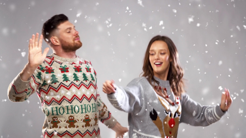 Celebration, fun and holidays concept - happy couple wearing knitted sweaters dancing at christmas party | Shutterstock HD Video #1039530443