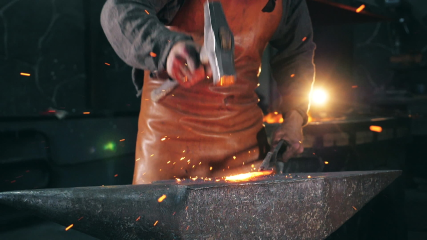 Blacksmith is using hammer to forge metal | Shutterstock HD Video #1039532246