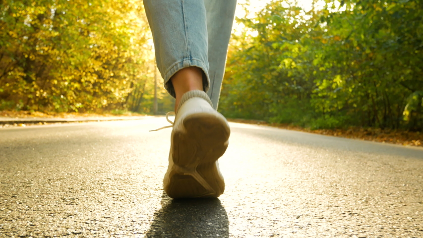 Walks in forest girl in jeans and cute trainers step on park autumn | Shutterstock HD Video #1039534328