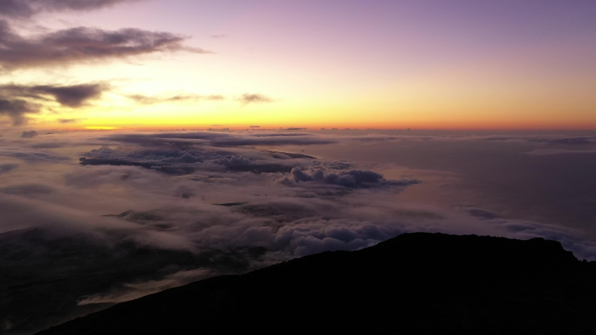 Drone Aerial view above the clouds in the Pico Mountain crater, Açores, with a purple sky due to volcanic dust.