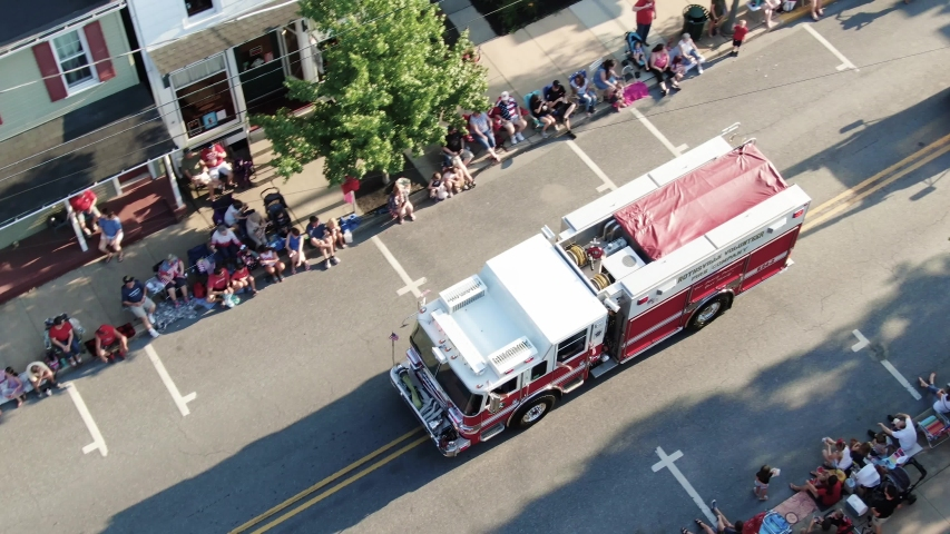 Lititz , PA / United States - 07 04 2019: Aerial turn and top down shot of fire truck in Fourth of July parade, crowds line streets
