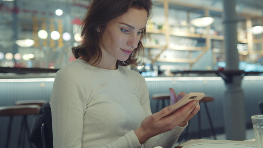 Attractive young brunette woman using smartphone device while sitting in urban cafe or vegan restaurant sharing post at her social media or personal blog, girl texting message enjoying free time  | Shutterstock HD Video #1039546880