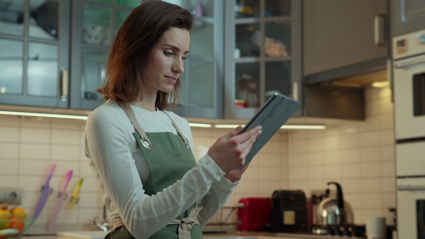 Side view of attractive young female novice cook using modern digital tablet device to search food blog in the internet with vegetarian recipes, gluten free and vegan recipes, Cinematic Shot  | Shutterstock HD Video #1039546946