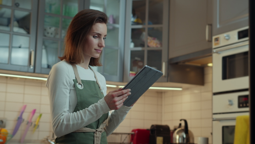 Side view of young beautiful woman using modern digital tablet device with touchscreen searching easy wholesome recipes including gluten free, dairy free, low carb, Vegetarian and Vegan Options | Shutterstock HD Video #1039546955