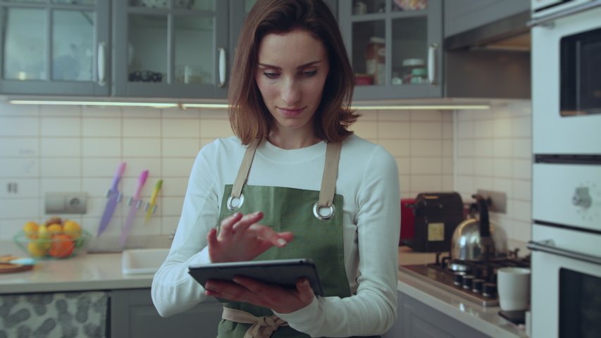 Happy young female amateur chef using modern digital tablet device with touch screen browsing social media or searching top tips for healthy meal recipes for dinner,  | Shutterstock HD Video #1039546964