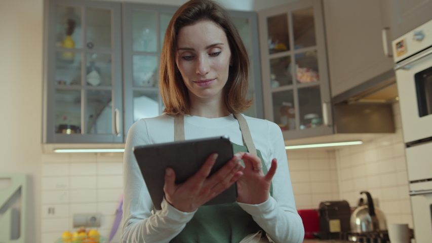 Positive Organized Housewife shares her top tips to meal at social media using digital tablet device with touch screen while stands in the kitchen, Healthy Vegan Recipes People Amateur Chef   Shutterstock HD Video #1039546970
