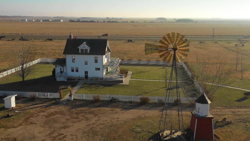 YORK, NEBRASKA - CIRCA 2018 - A drone aerial establishing shot of a classic farmhouse farm and barns in rural midwest America, York, Nebraska.