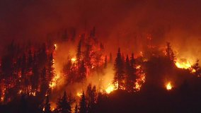 Aerial, tracking, drone shot, overlooking forest in flames, Alaskan wildfires destroying and causing air pollution, on a dark, summer night, in Alaska, USA